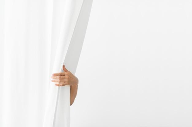 Hand die een wit gordijn opent