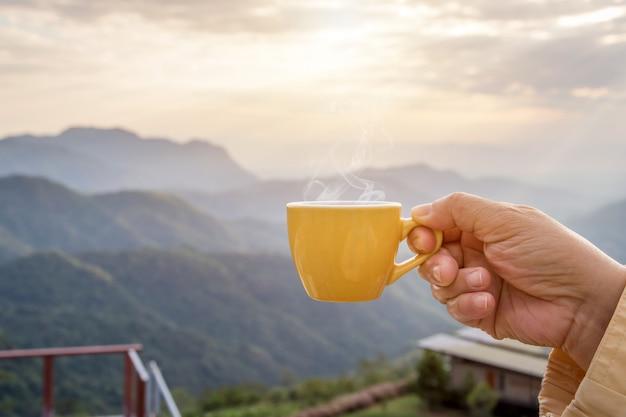 Hand die een witte kop hete espressomokken en aardmening houden van het berglandschap in de ochtend met zonlicht