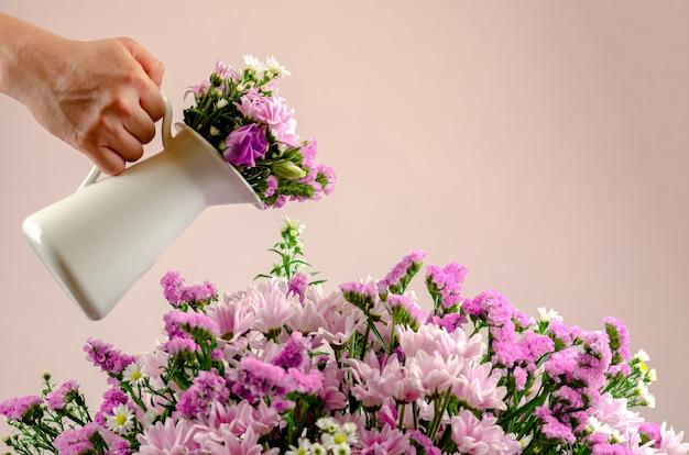 Hand die een witte pot houdt die het boeket van kleurrijke bloemen water geeft.