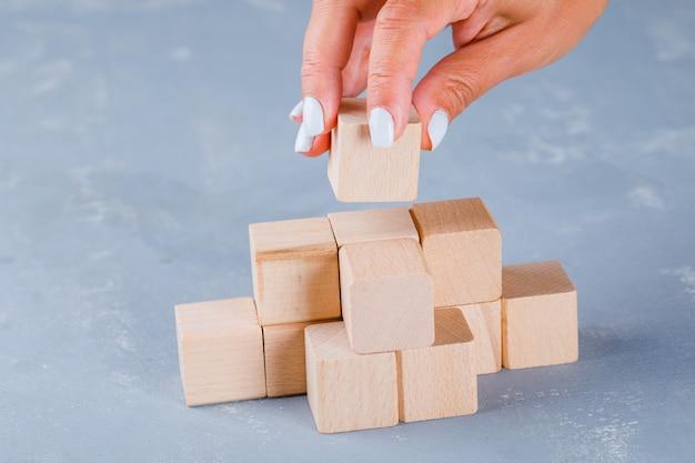 Hand die en houten kubussen zet stapelt