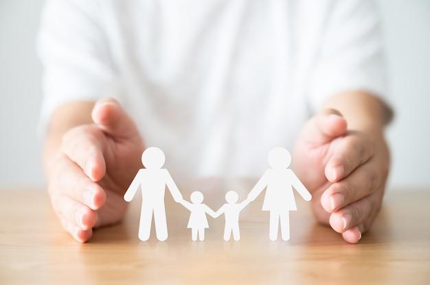 Hand die familie op houten tafel beschermt. gezondheidszorg en levensverzekeringsconcept