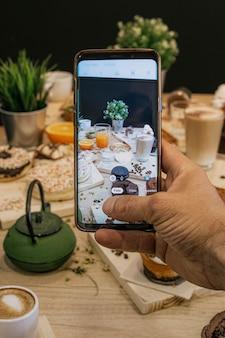 Hand die foto van een lijsthoogtepunt van cakes en voedsel op een houten lijst maakt