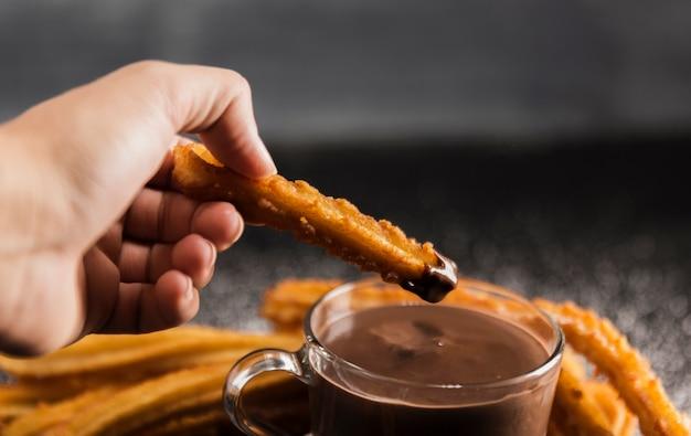Hand die gebraden churros met chocolade houdt