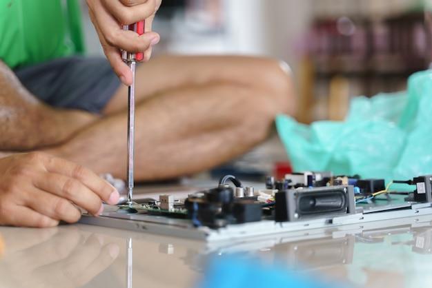 Hand die gebroken elektronische raad of pcb bevestigt