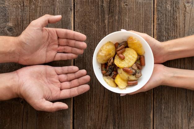 Hand die gedoneerde voerbak geeft aan behoeftige