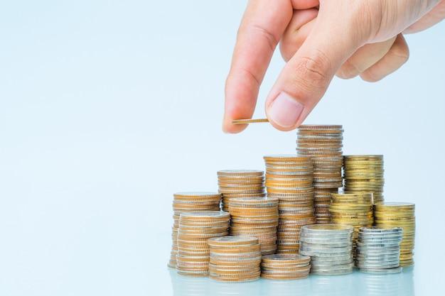 Hand die geld aan stapel van muntstuk zet, geldconcept te bewaren