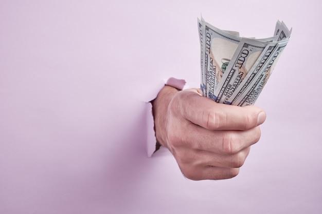 Hand die geld geeft door een gat