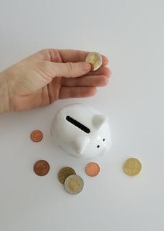 Hand die geldmuntstuk in spaarvarken stopt om geld te besparen. rijkdom, budget, investeringen, financiën concept. spaarpot, spaarpot op de witte achtergrond.