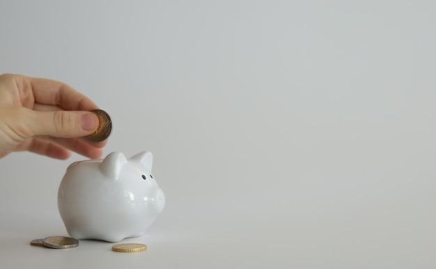 Hand die geldmuntstuk in spaarvarken stopt om geld te besparen. rijkdom, budget, investeringen, financiën concept. spaarpot, spaarpot op de zwarte achtergrond. vrije ruimte voor tekst, kopieer ruimte.