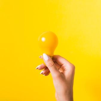 Hand die gele gloeilamp houdt tegen gekleurde achtergrond