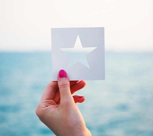 Hand die geperforeerde document stervorm met oceaanachtergrond houdt