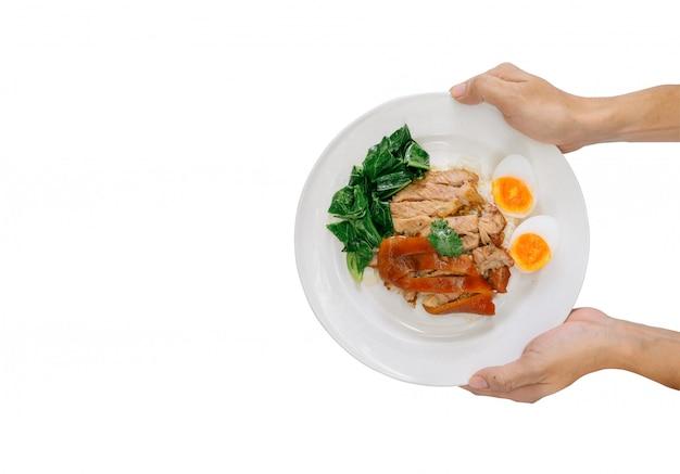 Hand die gestoofd varkensvleesbeen op rijst op witte achtergrond houden. heerlijk straatvoedsel, calorierijk voedsel, fastfood met veel vet.