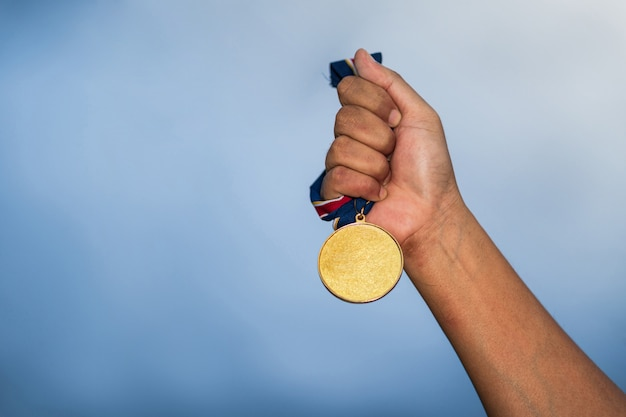 Hand die gouden medaille tegen bewolkte hemel houdt
