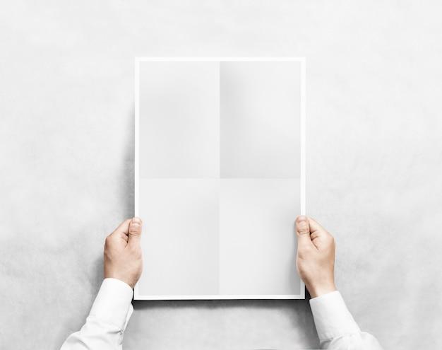 Hand die grijs leeg affichemodel houdt, geïsoleerd