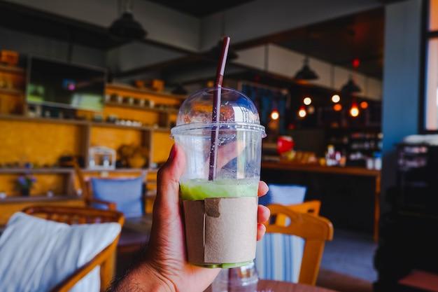 Hand die groene thee plastic kop in het milieu van de koffiewinkel houden