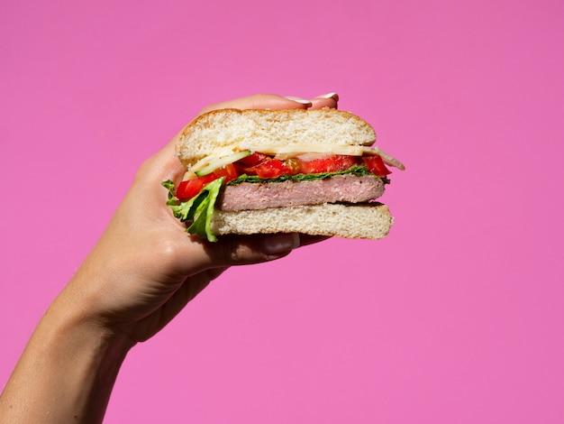 Hand die halve hamburger op roze achtergrond houdt