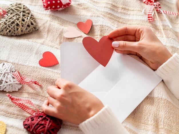 Hand die hart in envelop zet
