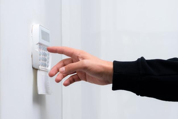 Hand die het alarmsysteemwachtwoord van een appartement, huis of bedrijfskantoor invoert.