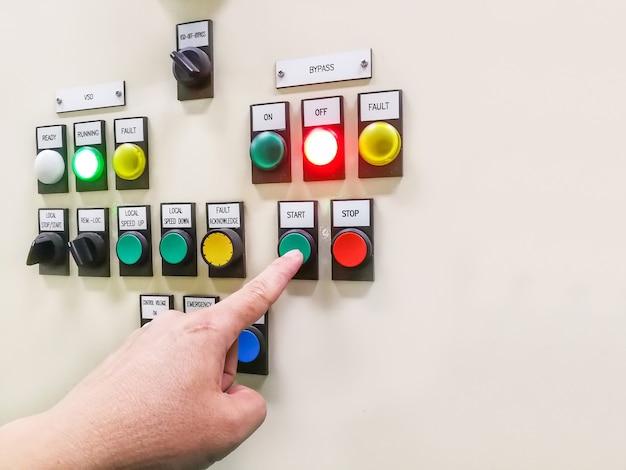 Hand die het bedieningspaneel van de industriële installatie vasthoudt en de knop in de elektrische keuzeschakelaar indrukt of draait, knopschakelaar motorcontrolecentrumkast