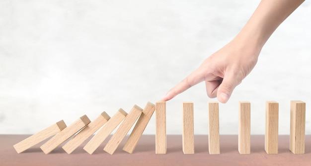 Hand die het domino-effect op houten blokken tegenhoudt