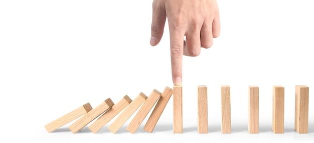 Hand die het domino-effect stopt, gestopt door unieke, zakelijke ideeën