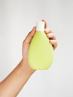 Hand die het gele model van de lotionfles houdt