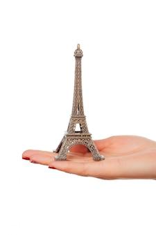 Hand die het kleine beeldje van de toren van eiffel houdt