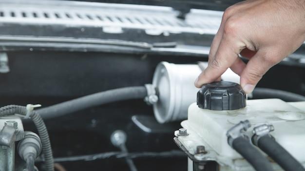 Hand die het niveau van de motor van de koelvloeistof van een auto controleert.