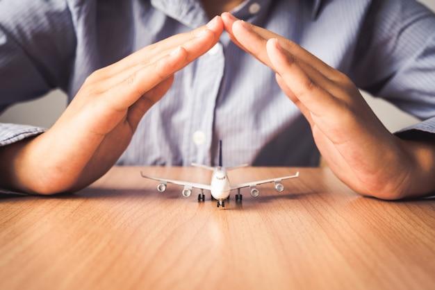 Hand die het pictogram beschermt een vliegtuig - van verzekering voor reis