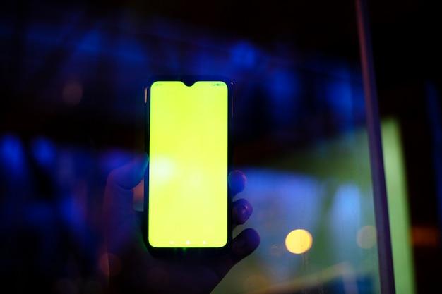 Hand die het scherm van de mobiele telefoon 's nachts toont met blauwe lichten achtergrond!