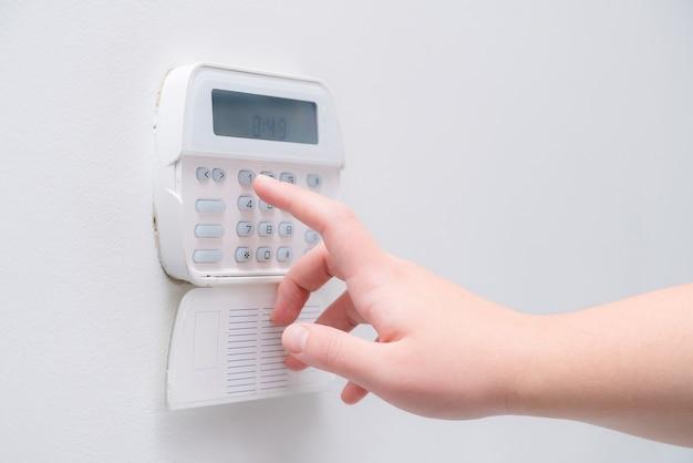 Hand die het wachtwoord van het alarmsysteem invoert.