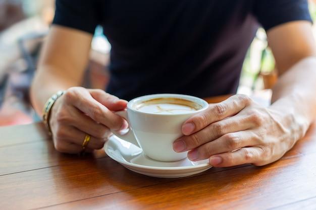Hand die hete koffiekop houdt