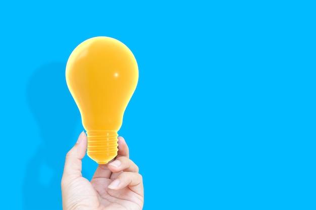 Hand die househand houden die gloeilamp gele pastelkleur op blauwe achtergrond houden