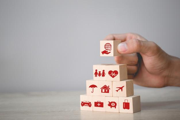 Hand die houtblok het stapelen met pictogramverzekering schikken: auto,