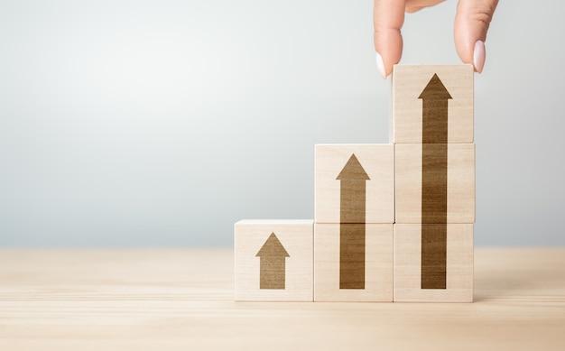 Hand die houtblok met pijl-omhoogpictogram schikt. bijgesneden hand van persoon stapelen houten blokken op tafel. business concept groei succes proces