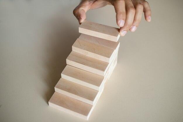 Hand die houtblokken schikt die als staptrede worden gestapeld. laddercarrièrepadconcept voor het succesproces van de bedrijfsgroei, ruimte kopiëren