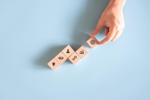 Hand die houtblokken schikt met bedrijfspictogrammen op lichtblauwe achtergrond