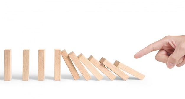 Hand die houten blok duwen en domino-effect beginnen