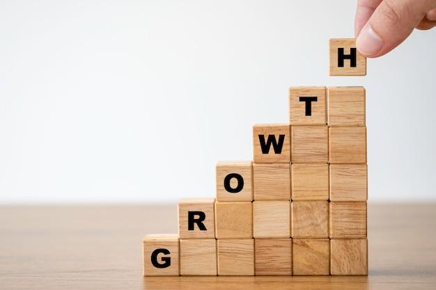 Hand die houten blokjes zet die de formulering van de het schermgroei drukken. doel van investeringen en bedrijfsgroei concept.