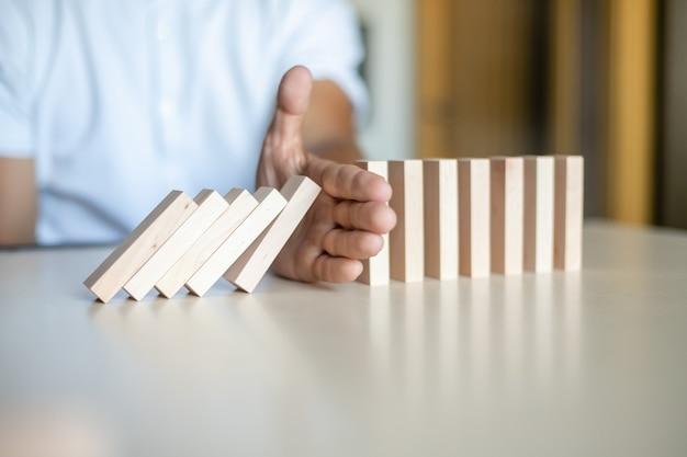 Hand die houten blokken tegenhoudt om in de lijn van domino te vallen