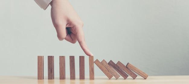 Hand die houten domino bedrijfscrisiseffect of concept van de risicobescherming tegenhoudt