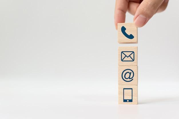 Hand die houten het symbooltelefoon, e-mail, het adres en de mobiele telefoon van de blokkubus zetten. website-pagina neem contact met ons op of e-mailmarketingconcept