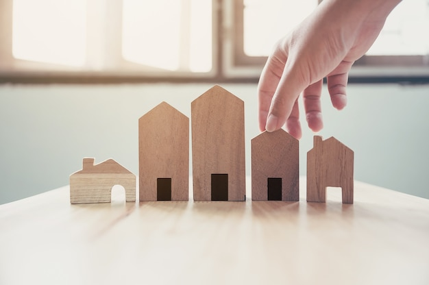 Hand die houten huismodel kiest