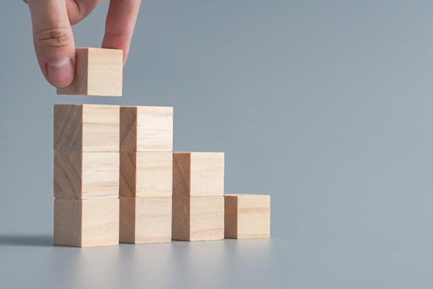 Hand die houten kubus schikken die als vorm van de tredestap, de bedrijfsgroei en beheersconcept stapelen