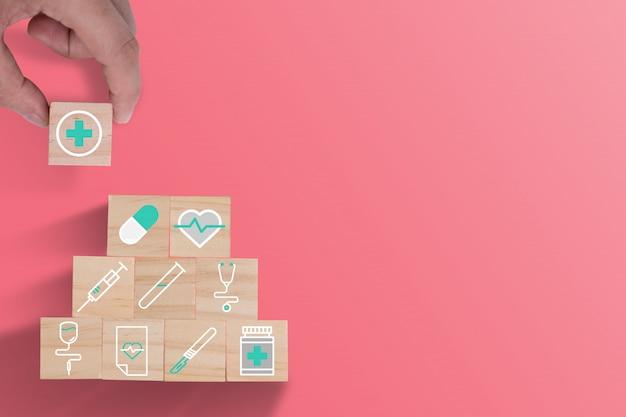 Hand die houten kubussen het stapelen van gezondheidszorggeneeskunde en het ziekenhuispictogram op mooie roze achtergrond zetten. zorgverzekeringen en investeringen.