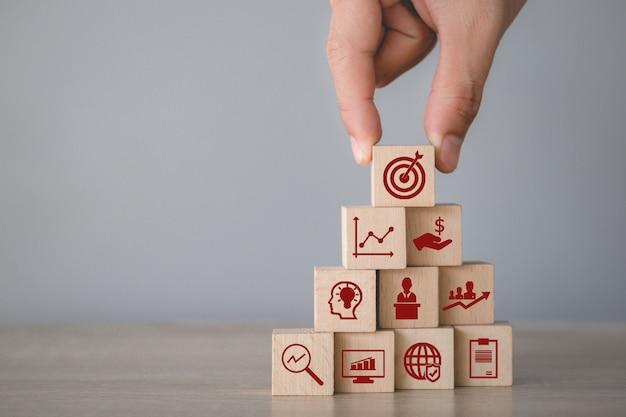 Hand die houtsnede het stapelen met pictogrampijl en zaken schikken, die het bedrijfsconcept richten.