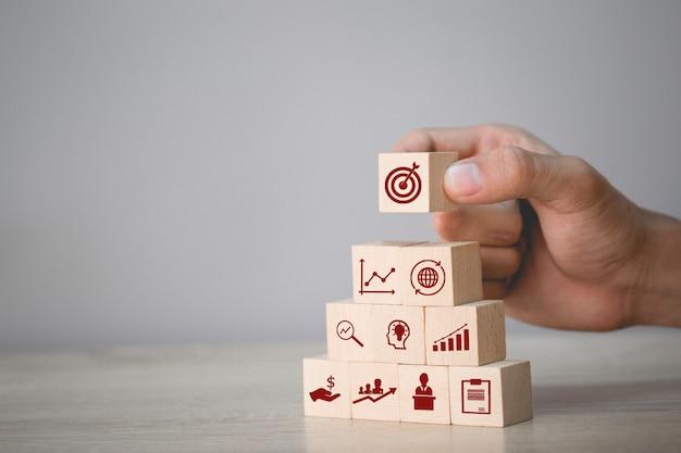 Hand die houtsnede schikken die met pictogrampijl en zaken stapelen, die het bedrijfsconcept richten.