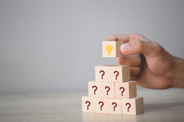 Hand die houtsnede schikken die met pictogramvraagteken en lamp stapelen, die met vraagtekenconcept denken.