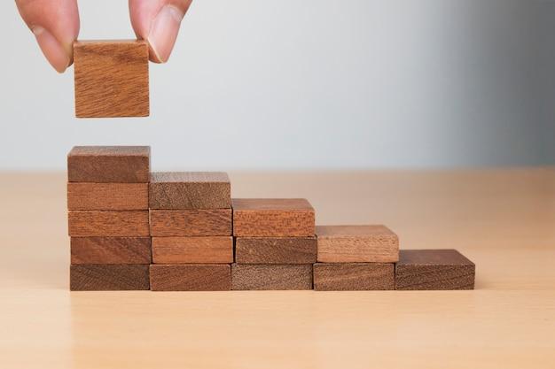 Hand die houtsnedestapel stapelen als staptrede op houten lijst. bedrijfsconcept voor groeisuccesproces. kopieer ruimte