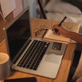 Hand die in een notitieboekje naast laptop schrijft